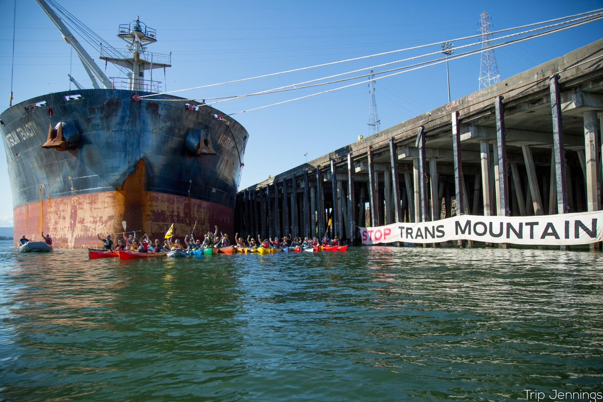 "A giant oil ship at left is surrounded by protesters in small kayaks. Their banner reads ""Stop Trans Mountain"""