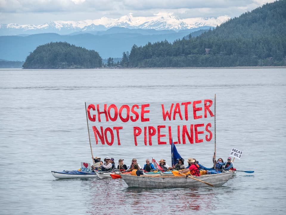 "A group of kayakers hold a large banner reading ""Choose Water Not Pipelines."""